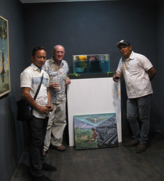 "Henri Cainglet and Edwin Toth standing with Lemuel Cunanan artwork on the floor ""New Paradise"", 22""x23"", oil on canvas, 2015. Lemuel comments"" The world is making a move for its own development but on the other side, the changes itself is the hidden antagonist in disguise. We are the co called ""changes"" of our own world, the wrecker of its own land, but we should be the one who will save it from its disastrous changes. My goal is to maintain the beauty of the world itself to bring back what has been lost, and to see what lies beyond our hands that will someday lead us with our own. With our own paradise...‬ Map for Climate Show Opening, Archivo 1984 Gallery. #mapforclimate"
